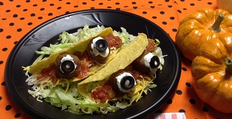 plate with two hardshell tacos with olives that look like eyeballs