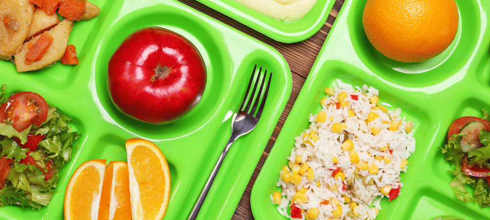 school lunch trays with fresh produce on table