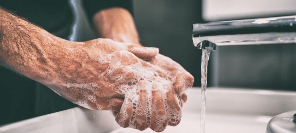 man washing hands with soap and water