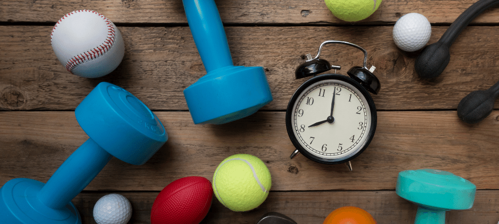 variety of fitness equipment, sports balls, and a clock on a wood background