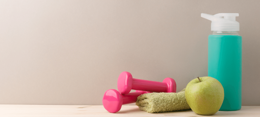 small dumbbells with apple, water bottle, and towel