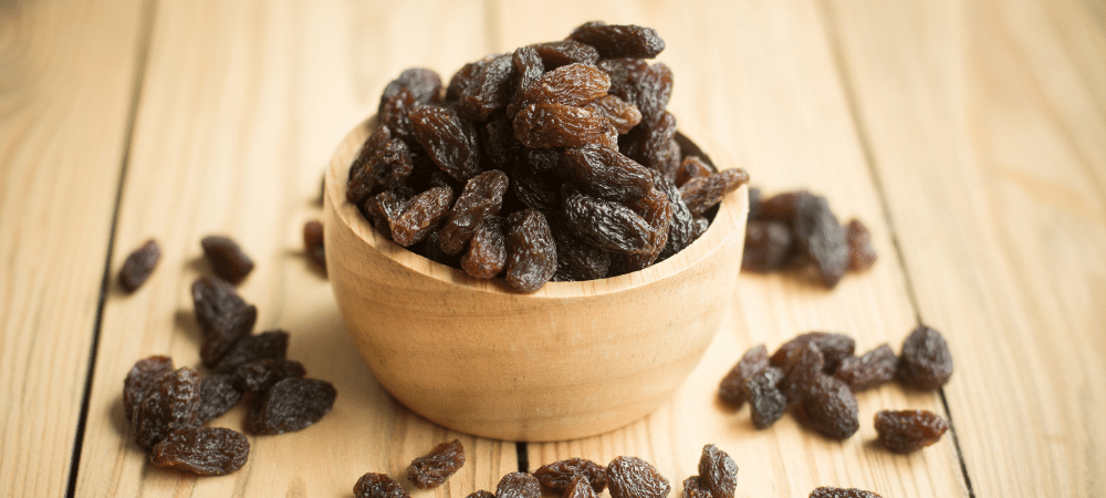 raisins in a wooden bowl on a table