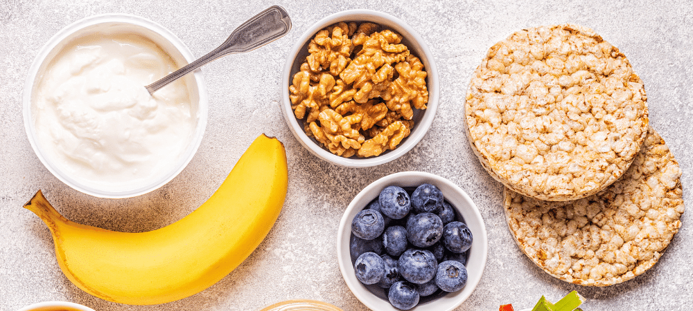 healthy snacks such as yogurt, banana, blueberries, walnuts, and rice cakes