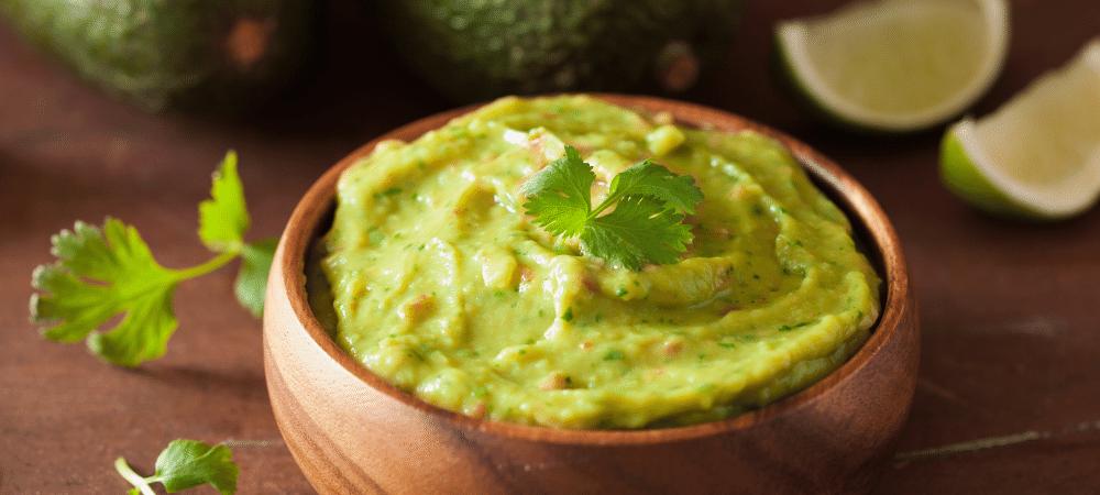 guacamole dip in a wooden bowl