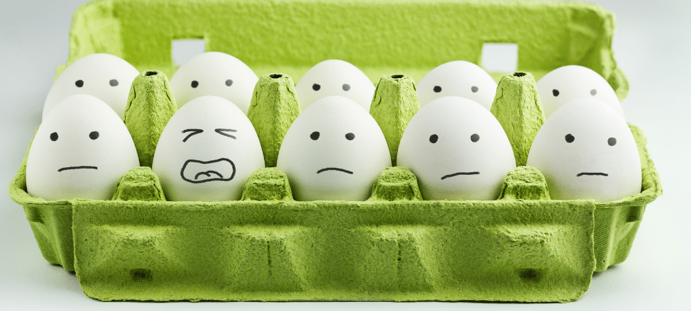 variety of stressed faces drawn on eggs