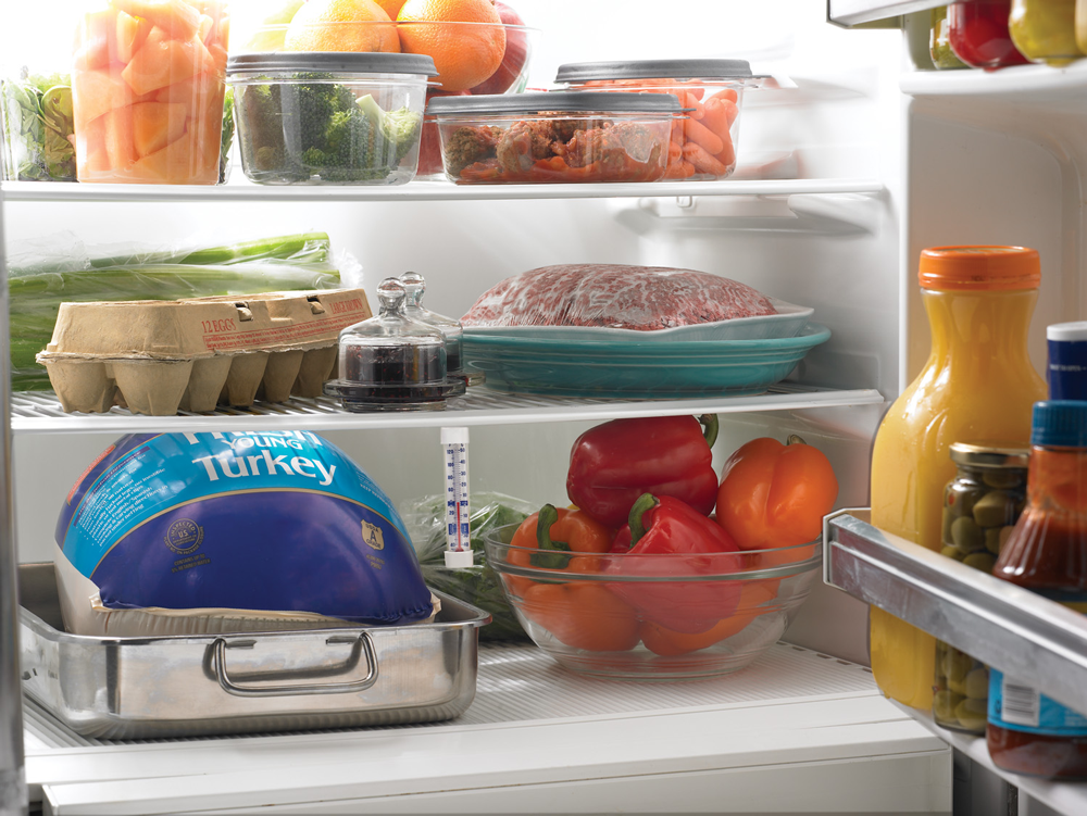 inside of refrigerator with a thermometer and containing fruit, vegetables and protein foods