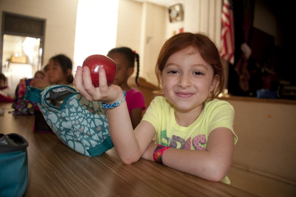girl in school lunchroom with an apple