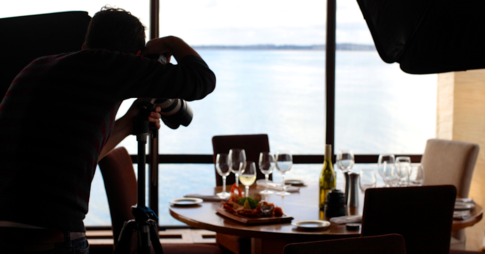 man photographing food on a table