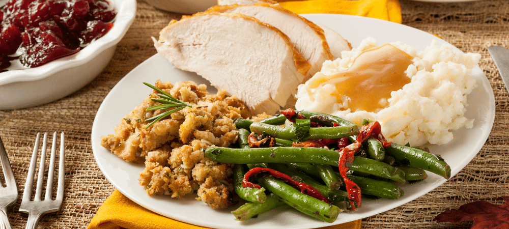 A Thanksgiving dinner plate with turkey, stuffing, mashed potatoes and gravy, and green beans.