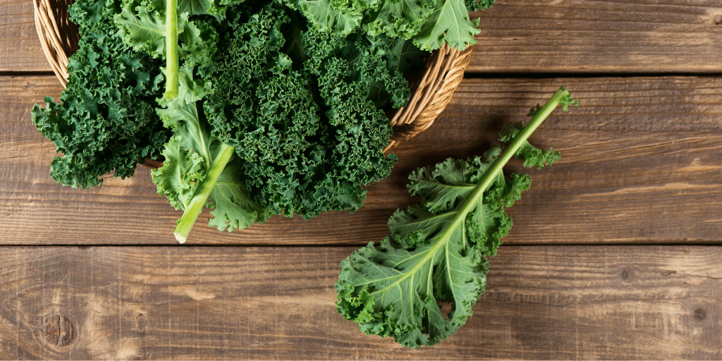 raw kale leaves on a wooden table