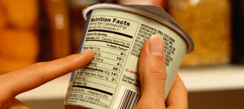 person reading a nutrition facts label on a food item