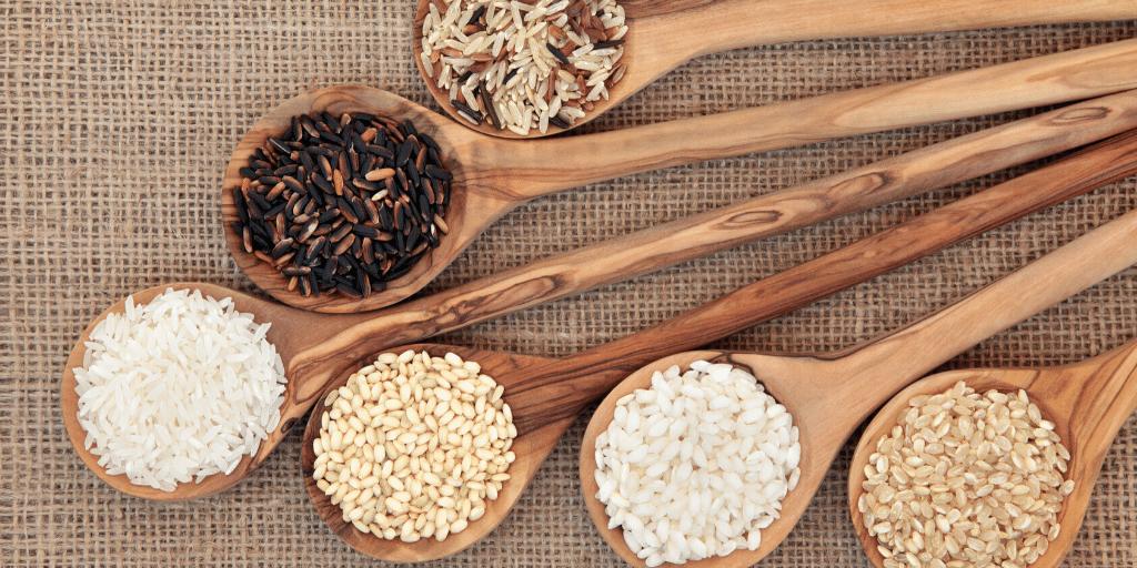 Rice varieties in olive wood spoons.