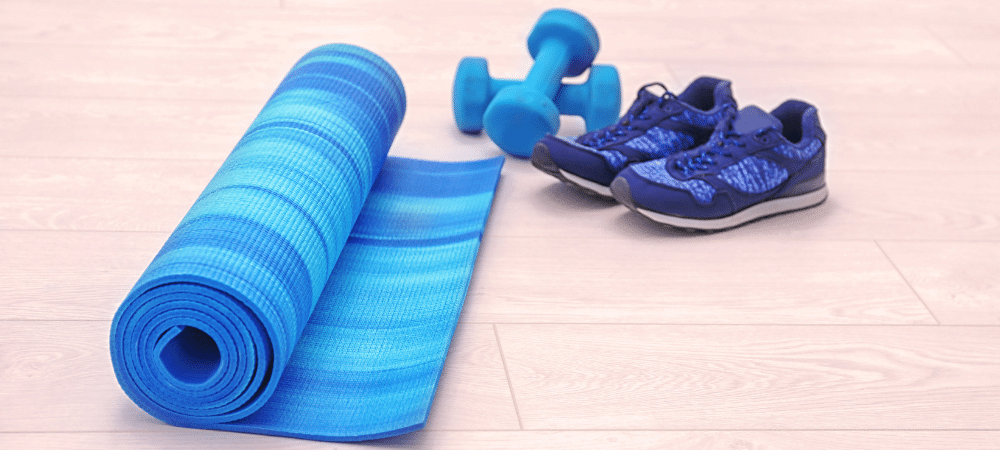 yoga mat, weights, and tennis shoes on a wooden floor