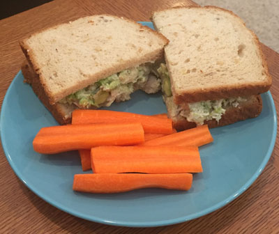 Chicken avocado sandwich on a plate with carrot sticks