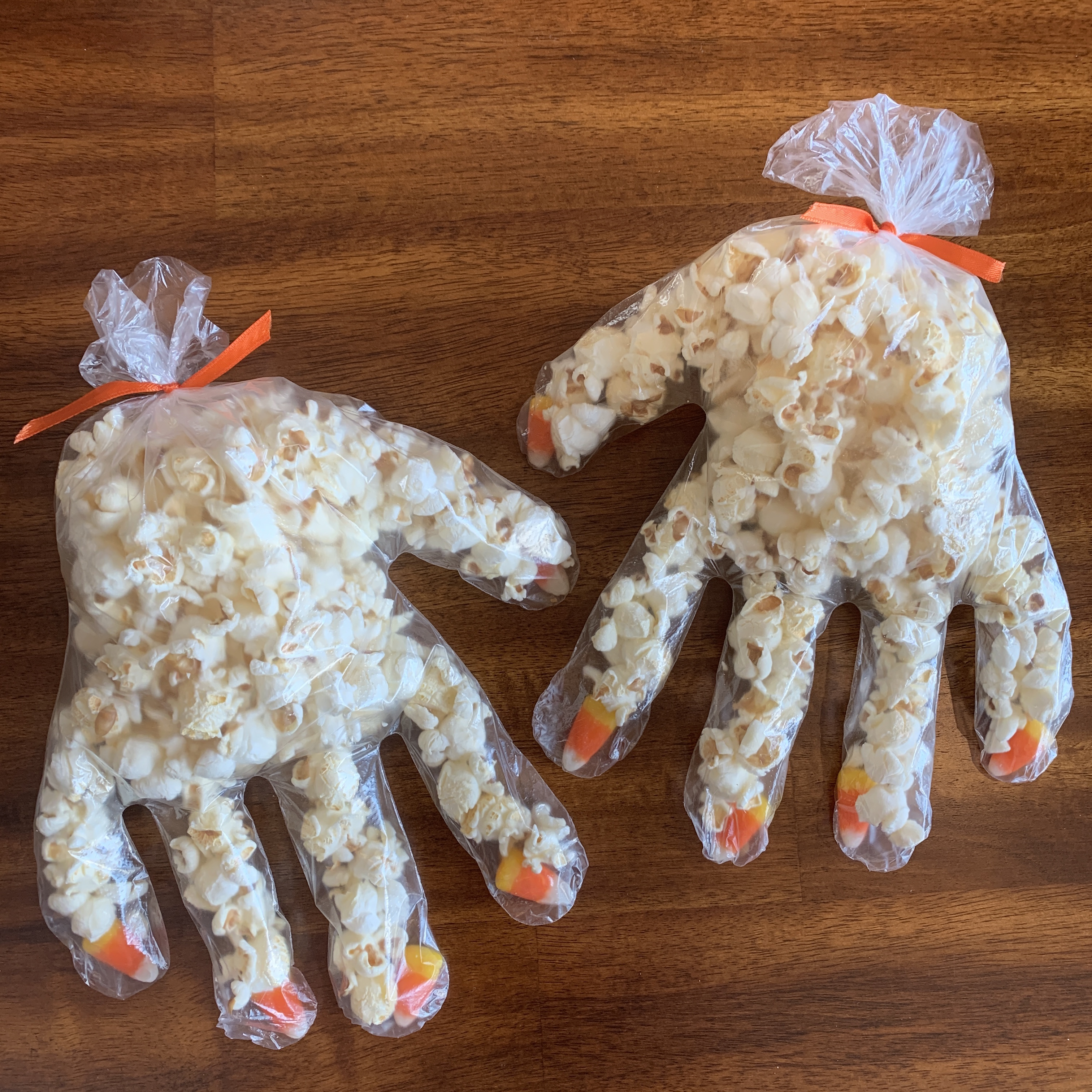 food safe plastic glove with a candy corn for each fingernail and filled with popcorn