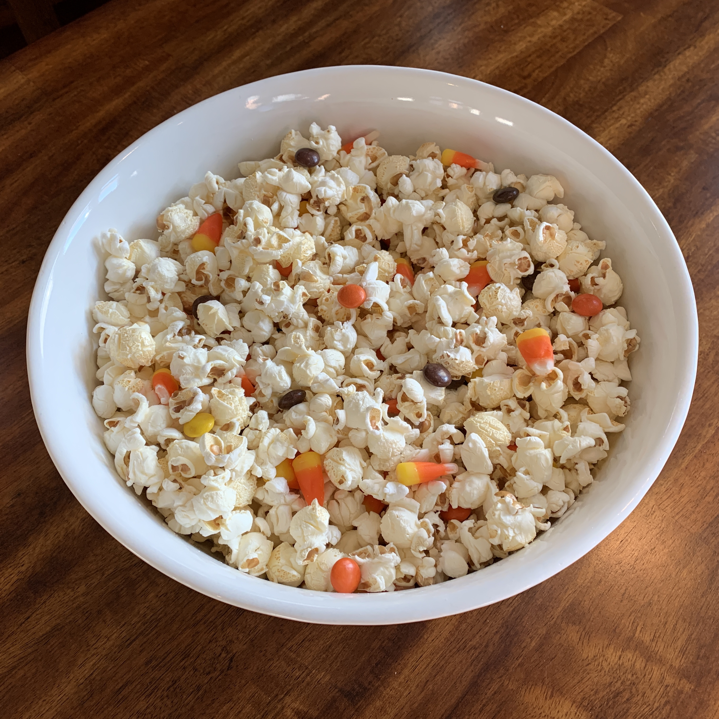 popcorn mixed with candy corn and orange, brown, and yellow candy pieces filled with peanut butter