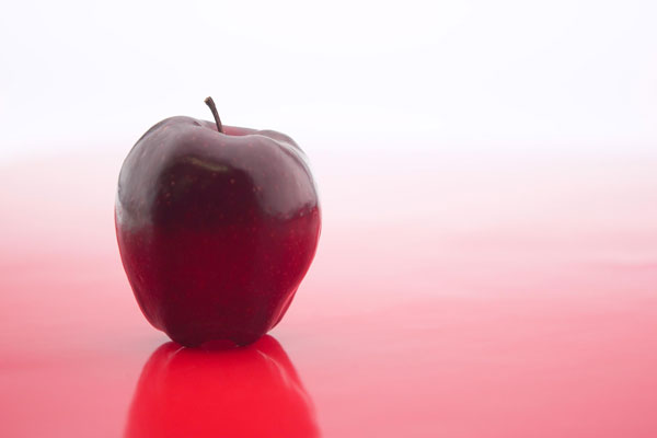 an apple sitting on a reflective red surface