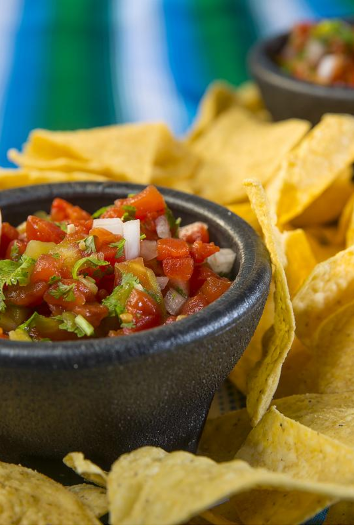 Salsa in a black bowl surrounded by tortilla chips