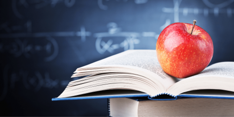 apple on a book in a classroom with a blackboard in the background
