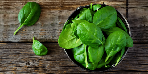 bowl of spinach on a wooden table