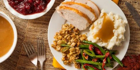 a plate of turkey, mashed potatoes and gravy, stuffing, and green beans