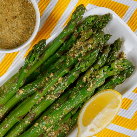 asparagus on a white plate with mustard vinaigrette on top